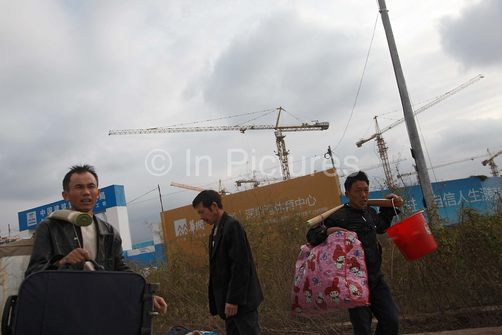 Migrant workers carrying their belonging on bamboo poles leave a construction site in Shenzhen, China on 17 November 2009.