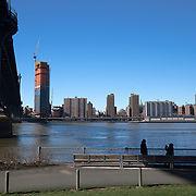 Couple taking photo  with child beneath the Manhattan bridge on the Brooklyn side.  Construction of One Manhattan Square can be seen rising across the East River.