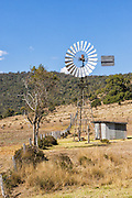 Windmill and tin pump shed in field surrounded by hills near Bell, Queensland, Australia <br />