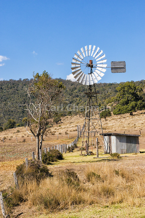 Windmill and tin pump shed in field surrounded by hills near Bell, Queensland, Australia <br /> <br /> Editions:- Open Edition Print / Stock Image