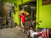 05 OCTOBER 2012 - BANGKOK, THAILAND:  A man carries large sacks of rice from a Chinese owned rice wholesaling business to a waiting handcart so he could deliver it to a customer. Thailand is one of the largest producers of rice in the world.      PHOTO BY JACK KURTZ