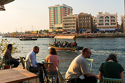 People in cafe beside The Creek at sunset in Old Dubai, United Arab Emirates.