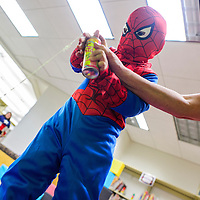 092714       Cable Hoover<br /> <br /> Spiderman Dante Harvey gets a hand with his web shooter from library assistant Jobi Herrera during the superhero party at the Octavia Fellin Public Library Children's Branch in Gallup Saturday.