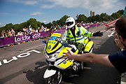 London, UK. Saturday 28th July 2012. On Putney Bridge in London, a police motorcycle rider helps to warm up the crowd, high fiving them on the way past prior to the Men's Team Road Race.