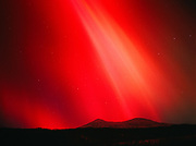 Brilliant red aurora in the evening hours during the geomagnetic storm on November 5, 2001, view southwest over the Talkeetna Mountains, Little Susitna River valley, Alaska.