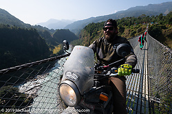 Tattoo artist Justin Big Meas Wilson riding a Royal Enfield Himalayan on the Kushma - Gyadi suspension bridge over the Modi River (the highest, at 384 feet, and longest, at 1,128 feet, suspension bridge in Nepal) duringMotorcycle Sherpa's Ride to the Heavens motorcycle adventure in the Himalayas of Nepal. On the sixth day of riding, we went from Tatopani to Pokhara. Saturday, November 9, 2019. Photography ©2019 Michael Lichter.