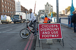 © Licensed to London News Pictures. 01/10/2016. LONDON, UK.  A cyclist on the pavement at Tower Bridge. Tower Bridge closes to traffic today for three months for major renovations and repair. Pedestrians are still able to walk across the bridge. Photo credit: Vickie Flores/LNP