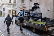 Two workmen walk past the second of two giant Christmas decoration bears which are being offloaded from a sub-contractor's lorry and delivered to the foyer of the Cafe Royal in Air Street, on 1st December 2020, in London, England. The bears have been manufactured by Romanian Eugeniu Dumneanu's Art-Grass company, a synthetic grass and turf provider specialising in the covering of surfaces and instillations with artificial grass and Astroturf.