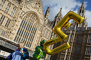 A woman protestor holds some balloons with the letters E and U during a pro-EU brexit protest opposite Parliament, on 11th March 2019, in Westminster, London, England.