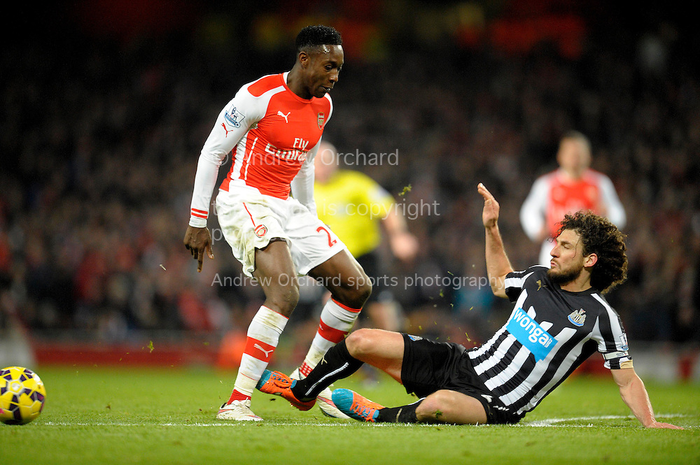 Fabricio Coloccini, the Newcastle United capt slides in to tackle Danny Welbeck of Arsenal. Barclays Premier league match, Arsenal v Newcastle Utd at the Emirates Stadium in London on Saturday 13th December 2014.<br /> pic by John Patrick Fletcher, Andrew Orchard sports photography.