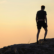 "Male silhouette on hiest hill of the Zhiguli mountains on sunset. Russian National Park ""Samarskaya Luka"""