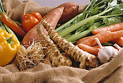 Still life with spring onion, yam, ginger, parsley and an assortment of peppers of different types and colours on jute