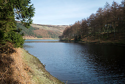 """The View East from the West bank of the Derwent Reservoir in Derbyshire, England is the middle of three reservoirs in the Upper Derwent Valley, the higher reservoir being Howden to the North and the lower being Ladybower to the south. Between them they provide practically all of Derbyshire's water, as well as to a large part of South Yorkshire and as far afield as Nottingham and Leicester.<br /> Begun in 1902 this neo-Gothic solid masonry dam wall is built from huge stones that were transported along a specially created railway from the quarries at Grindleford. Over 1,000 workers lived in a specially constructed and self-contained town of Birchinlee also known as """"Tin Town"""". Derwent reservoir began being filled in November 1914, and overflowed for the first time in January of 1916. Covering an area of 70.8 hectares (175 acres) and at its deepest point is 34.7 metres (114 ft) the dam can support a total of 9.64 million cubic metres of water.<br /> For 6 weeks during the Second World War the reservoir was used by the pilots of the 617 Squadron """"the Dambusters"""" to practice their low-level flying skills needed for Operation Chastise, because of the Derwents similarity to the operations German target. In for 2 weeks in 1954 the the sound of Lancaster bomber engines could be heard again over the Derwent as the reservoir stood in for the German dams a second time. This time for the filming of the """"The Dambusters"""" starring Richard Todd as Guy Gibson. The west tower of the dam wall is home to Derwent Valley Museum and includes a permanent memorial to 617 Squadron to which is visible even when the Museum is closed. <br /> <br /> 22  March 2015 Image © Paul David Drabble www.pauldaviddrabble.co.uk"""