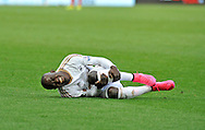 Swansea City's Modou Barrow rolls on the ground in pain injured after being fouled by Everton's Kevin Mirallas late in the second half for which Mirallas is sent off.<br /> Barclays Premier League match, Swansea city v Everton at the Liberty Stadium in Swansea, South Wales on Saturday 19th September 2015.<br /> pic by Phil Rees, Andrew Orchard sports photography.