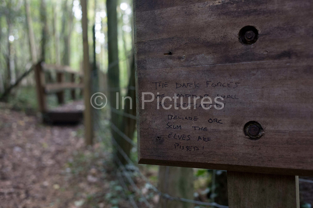 A message written by somebody, on a sign in a north Somerset forest. With a wooden bridge seen in the distance and autumnal trees out of focus behind, we see the notice board with the handwritten message that refers to the fictional story Lord of the Rings in which Orcs were the most commonplace villains serving the Dark Powers in all of Tolkien's Mythology and Elves were the first children of Eru, the One, whom they called Ilúvatar. The Elves are not subject to disease or physical aging, though they could be killed by violence or by wasting away and losing the will to live. They were otherwise immortal.