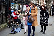 Passers by give money to a busker. London.