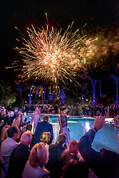 Fireworks burst above the crowd as models parade Armani fashions pool-side, during the Armani Casa Grand Opening celebration.
