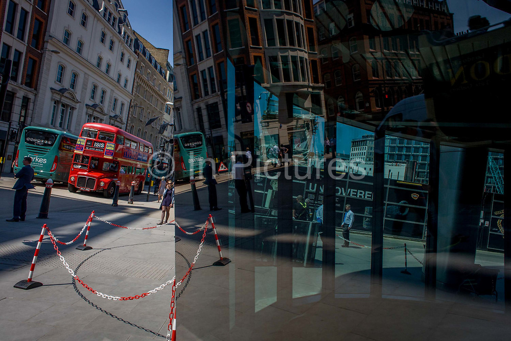Londoners seen reflected in multiple plate glass windows on a busy summer lunchtime, in the Square Mile, the capital's historic financial district. As pedestrians walk to and from their surrounding offices, a red London Rouetmaster bus continues its journey on its inner-city route past the vertical columns of steel. A red and white plastic chain barrier prevents them from entering the zone where, above - workers are cleaning an upper floor. The large windows are located on the corner of Cannon Street and Walbrook, both ancient thoroughfares in this ancient city, dating back to before Roman occupation.