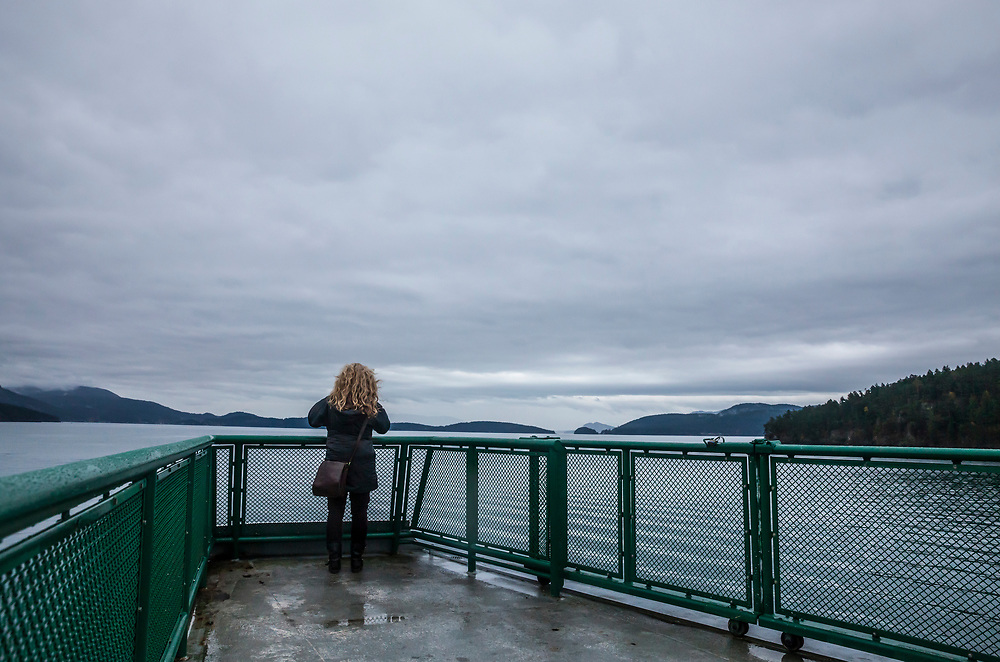 A woman stands on the observation deck  a Washington State Ferry taking a picture as it sails through the San Juan Islands, Washington, USA.
