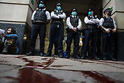 Metropolitan Police officers stand over fake blood sprayed around the entrance to the Department for Transport by activists from HS2 Rebellion, an umbrella campaign group comprising longstanding campaigners against the HS2 high-speed rail link as well as Extinction Rebellion activists, during a protest on 4 September 2020 in London, United Kingdom. Activists glued themselves to the doors and pavement outside the building and sprayed fake blood around the entrance during a protest which coincided with an announcement by HS2 Ltd that construction of the controversial £106bn high-speed rail link will now commence.