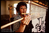 Navajo woman weaves rug on loom in her home on Navajo Reservation near Farmington. New Mexico