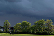The dark skies of an approaching rain storm approach a dog walker in Ruskin Park in Lambeth, south London, on 24th May 2021, in London, England.