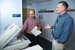 Men in office with photocopier.