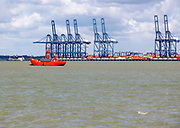 Cranes at Trinity terminal, Port of Felixstowe from Harwich, England, UK red lightship at mooring