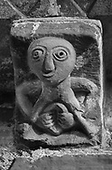 The Stone Bestiary - Black and white photo art print of The Stone Bestiary - Black and white photo art print of Norman Romanesque exterior corbel no 28 (similar style to No 44) - sculpture of a female exhibitionist known as a Sheela-na-gig. The sculpture shows a female with a huge round head and puny body with her hand holding open a grossly enlarged vulva. It seems unlikely that this image is of a pornographic nature because it is on a church, and is more likely a warning against the temptations of women. The Norman Romanesque Church of St Mary and St David, Kilpeck Herefordshire, England. Built around 1140 .<br /> <br /> Visit our LANDSCAPE PHOTO ART PRINT COLLECTIONS for more wall art photos to browse https://funkystock.photoshelter.com/gallery-collection/Places-Landscape-Photo-art-Prints-by-Photographer-Paul-Williams/C00001WetsxVxNTo