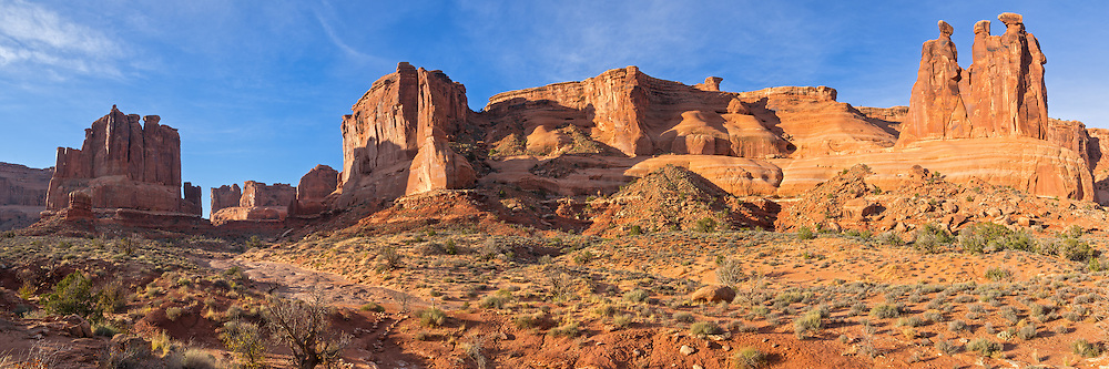 "The courthouse towers are a large rock formation in the middle of Arches National Park. The three spires on the right are known as the ""Three Gossips"". The early morning light gave the scene more depth and even brighter colors."