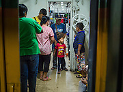 11 APRIL 2015 - BANGKOK, THAILAND: A boy and his father walk through a train bound for the Cambodian border. More than 130,000 passengers streamed through Bangkok's main train station Friday ahead of Songkran, Thailand's traditional new year celebration. Songkran will be celebrated April 13-15 but people started streaming out of Bangkok on April 10 to go back to their home provinces.    PHOTO BY JACK KURTZ