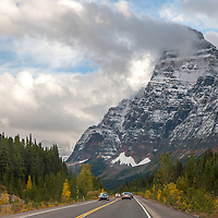 Cars drive below the Canadian Rockies on the Icefields Parkway. Mount Chefren background.