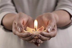 Woman holding burning candle in hands, Bavaria, Germany