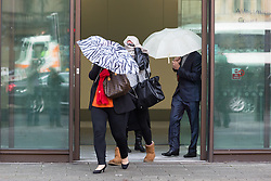 © Licensed to London News Pictures. 27/98/2015. London, UK. (L to R) Terri Robinson, Laura Perkins and Steven Robinson leaving Westminster Magistrates Court in London today. Four defendants: Brenn Walters (also known as Ben Perkins), Terri Robinson, Laura Perkins and Steven Robinson were granted unconditional bail at a hearing today after appearing charged under the Proceeds of Crime Act 2002 in connection with the Hatton Garden raid. All four defendants covered themselves from waiting press as they left the court in a taxi. Photo credit : Vickie Flores/LNP