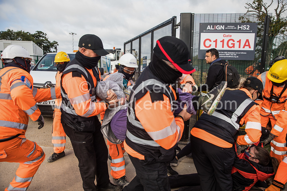 Harefield, UK. 12th September, 2020. Security guards working on behalf of HS2 forcibly remove environmental activists acting in solidarity with HS2 Rebellion from the road in front of a gate providing access to a site for the HS2 high-speed rail link. Anti-HS2 activists continue to try to prevent or delay works on the controversial £106bn HS2 high-speed rail link in the Colne Valley where thousands of trees have already been felled.