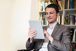 Mature businessman using digital tablet in an office, Bavaria, Germany