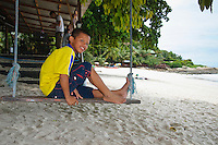 Boy on a swing at the beach, Koh Samet, Thailand