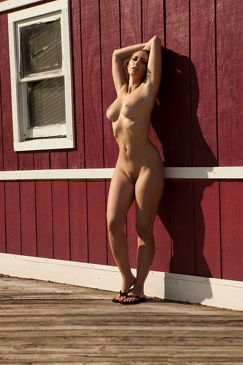 Nude woman leaning against an exterior rustic red wall with her arms above her head with bright sunlight