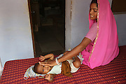 A young mother and child. Barefoot College medical clinic operates for the local communities..Barefoot College Tilonia, started by Bunker Roy in the 1970s. An organisation based upon creating economic self-empowerment and sustainable development initiatives, and self-sufficiency, for communities in the rural desert of Rajasthan, India. Energy autonomy with solar power capacitors, parabolic mirrors for cooking, solar powered water heating, and battery lanterns. Freshwater and irrigation through wells and desalination. A multitude of other economic initiatives run by grassroots Indian people, mainly women, where those who participate in, run the projects themselves. Many of them local lower castes, some physically handicapped, most with no paper qualifications, with support from others who gave up high flying money-making careers to be involved in working with poor rural communities. Mico-industries include solar lanterns, electric circuitry and lighting, crafts, textiles, children's toys, and sanitary towels. Also much emphasis on local and oral communications, radio, and puppetry. Now recognised internationally providing an educational resource most often directed towards communities of rural women worldwide.