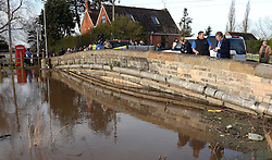 © Licensed to London News Pictures. 02/02/2014. Burrowbridge, UK Local people stand on a vridge over a flooded river. Burrowbridge on the Somerset levels today. The River Parrett broke its banks again at 9.15 am today 2nd February 2014. Photo credit : Jason Bryant/LNP