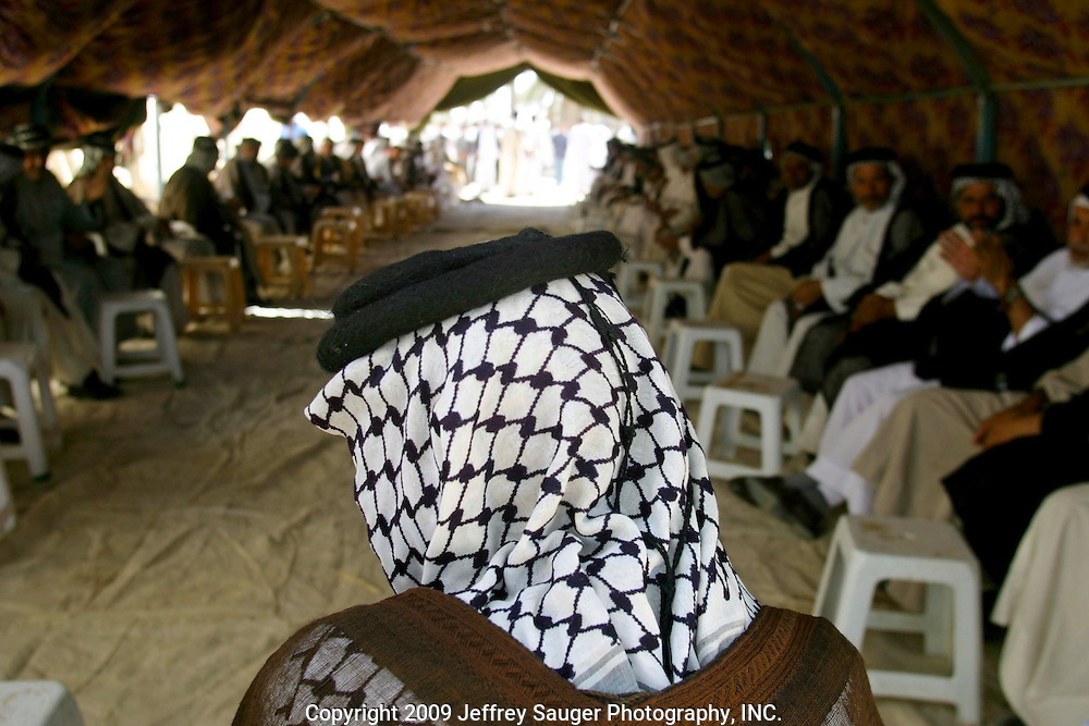 Guests consisting of tribal chiefs and members of the extended Al-kasid family gather at the Al-kasid family's Istikbal, or homecoming, in their home village Suq ash Shuyukh about 20 miles southeast of Nasiriyah, Iraq, Tuesday, July 29, 2003. ..When Malik Al-kasid's caravan approached, guns were fired to announce his family's arrival. The welcming party then, returns fire to welcome him. The two parties move toward each other dancing and shooting until they join in the middle where the Hawaies occurs. ..The Al-kasid family fled Iraq after the Gulf War and their part in the uprising against Saddam Hussein in 1991, spent 3 years in Rafa, Saudi Arabia and finally settled in Dearborn, MI. The family hasn't been home to Iraq in 13 years.