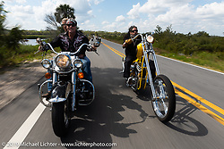 Jay Allen riding his Shovelhead with Danielle VanDeventer alongside Xavier Muriel riding a Little Twisted, the Twisted Tea Panhead built by Cycle Source Magazine through Tomoka State Park during Daytona Bike Week. FL. USA. Sunday March 18, 2018. Photography ©2018 Michael Lichter.