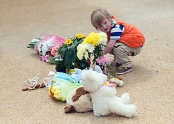 © Licensed to London News Pictures. 23/04/2014. New Malden, UK. A young boy looks at flowers. The scene in New Malden where a woman has been arrested after the discovery of three bodies of children in a house overnight. Photo credit : Stephen Simpson/LNP
