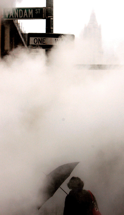 epa01096133 A man with an umbrella walks through steam rising from a construction site during a rain storm in New York, USA 21 August 2007.  In the background at top right is the outline of the Woolworth Building in lower Manhattan.  EPA/JUSTIN LANE