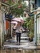 15 FEBRUARY 2015 - BANGKOK, THAILAND: Women walk through the rain to Sunday mass at Santa Cruz Catholic Church in the Kudeejeen neighborhood in Bangkok. Santa Cruz church was established in 1770  and is one of the oldest and most historic Catholic churches in Thailand. The church was originally built by Portuguese soldiers allied with King Taksin the Great. Taksin authorized the church as a thanks to the Portuguese who assisted the Siamese during the war with Burma. Most of the Catholics in the neighborhood trace their family roots to the original Portuguese soldiers who married Siamese (Thai) women. There are about 300,000 Catholics in Thailand in about 430 Catholic parishes and about 660 Catholic priests in Thailand. Thais are tolerant of other religions and although Thailand is officially Buddhist, Catholics are allowed to freely practice and people who convert to Catholicism are not discriminated against.      PHOTO BY JACK KURTZ