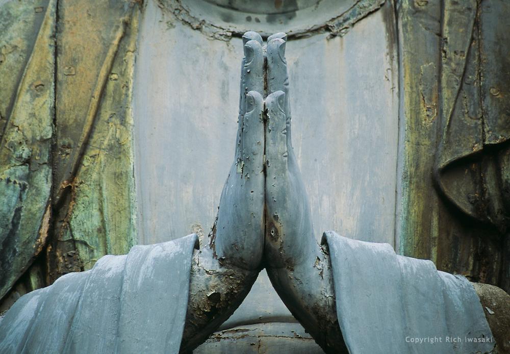Detail view of hands of bronze Buddha at Gokokusan Tennoji (temple), Yanaka district, Tokyo, Japan