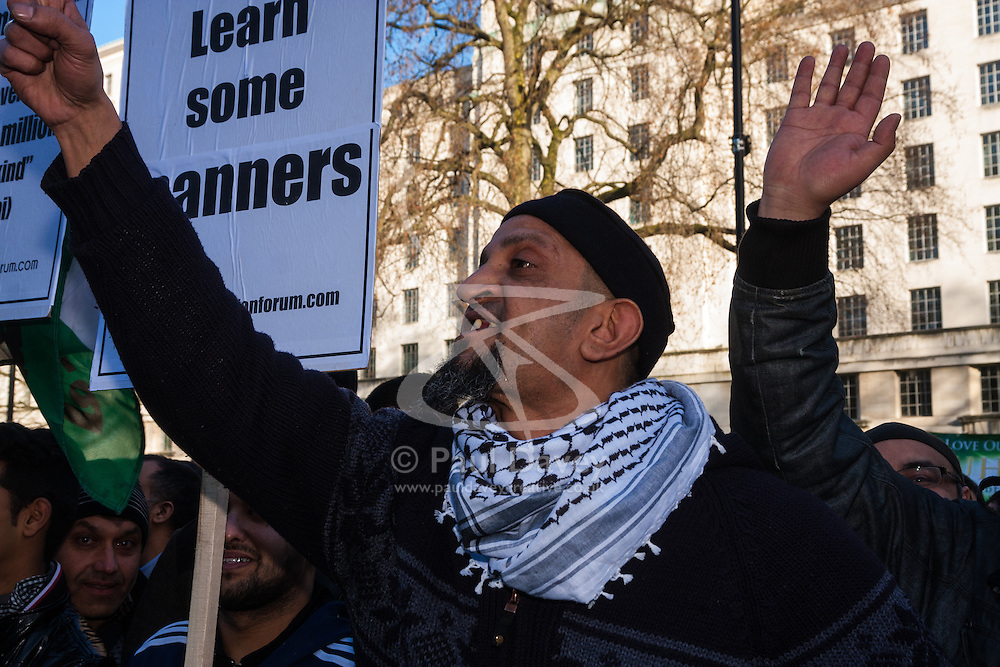 London, February 8th 2015. Muslims demonstrate outside Downing Street  to denounce the uncivilised expressionists reprinting of the cartoon image of the Holy Prophet Muhammad. PICTURED: An angry Muslim protester shouts at right wing anti-Muslim protesters across the street.