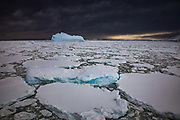 Dark storm cloud over iceberg and heavy pack ice, Penola Strait, Antarctic Peninsula.