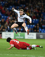 Paul Green of Rotherham Utd jumps over the tackle from Cardiff's Fabio Da Silva. Skybet football league championship match, Cardiff city v Rotherham Utd at the Cardiff city stadium in Cardiff, South Wales on Saturday 6th December 2014<br /> pic by Andrew Orchard, Andrew Orchard sports photography.