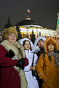 Moscow, Russia, 31/12/2005..Russians celebrate the lengthy New Year and Orthodox Christmas holidays. Crowds watch greetings from President Vladimir Putin broadcast on a giant television screen in Red Square.